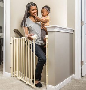 Best Baby Gates Top of Stairs: Evenflo Easy Walk Thru Top Of Stairs Gate with woman holding a toddler about to close the gate